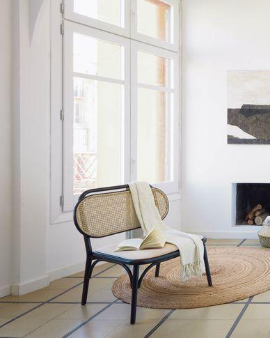 Poltrona Doriane in legno massiccio di olmo con finitura nera con seduta in tessuto.